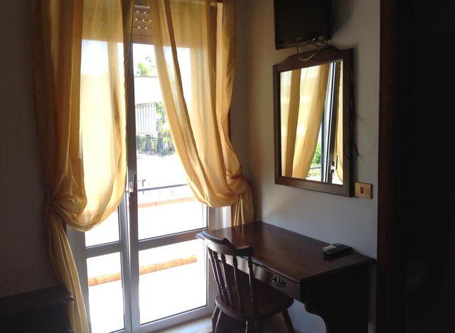 una stanza con una scrivania accanto una finestra