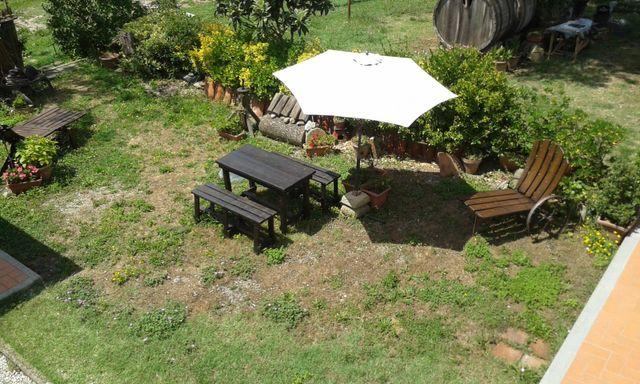 Vista dall'altro di un giardino con ombrellone bianco, tavolo in legno nero e poltrine di legno
