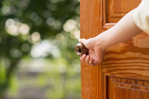 mano di una donna mentre apre una porta