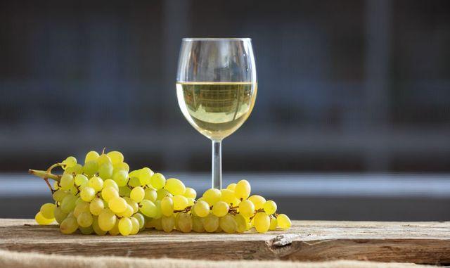 Grappolo d'uva verdi e coppa di vino bianco