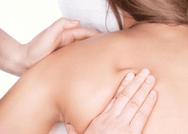 A therapist massaging a lady's shoulder