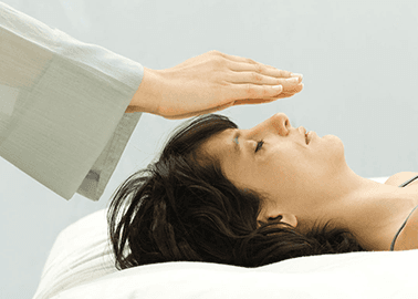 A therapist's hands hovering above a lady's head in a Reiki session