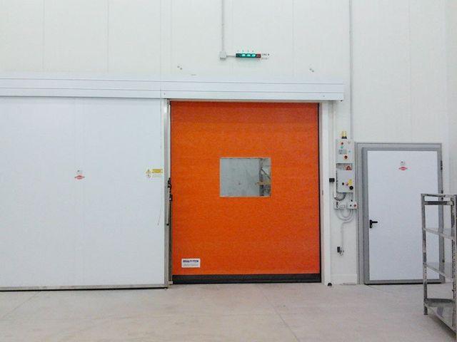 una porta arancione e accanto una bianca in un magazzino