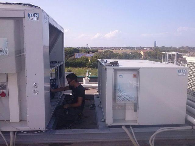 un operaio inginocchiato al lavoro su un impianto sopra un tetto
