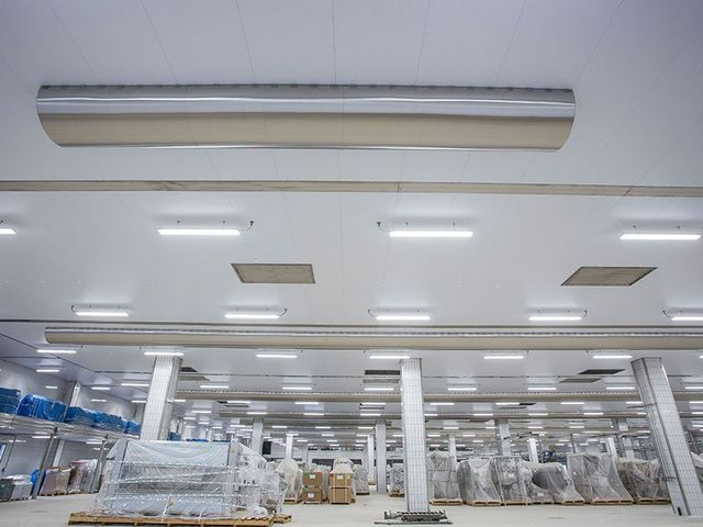 vista del soffitto di un magazzino, piu avanti delle colonne portanti e degli scatoloni su dei bancali con sopra il cellofan