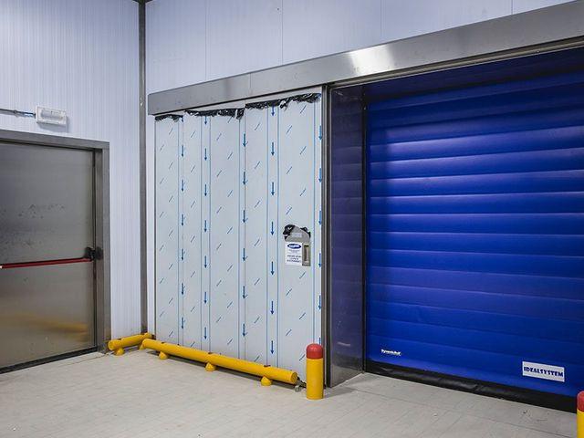 vista di una serranda blu e accanto un'altra porta all'interno di un magazzino