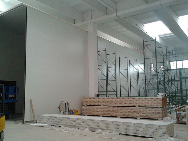 interno di un magazzino con dei bancali con dei materiali e dietro un impalcatura in ferro verde
