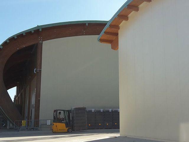 un uomo al lavoro su un muletto giallo all'esterno di due stabili con dei tetti in legno