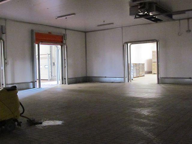 interno di un magazzino con due ingressi e sulla sinistra un macchinario giallo da pulizia
