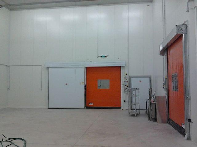 una porta bianca, una arancione e sulla sinistra degli oggetti all'interno di un magazzino