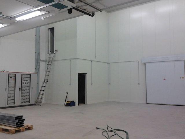 interno di un magazzino con sulla sinistra due quadri elettrici, dei bancali con del materiale e una scaletta in ferro