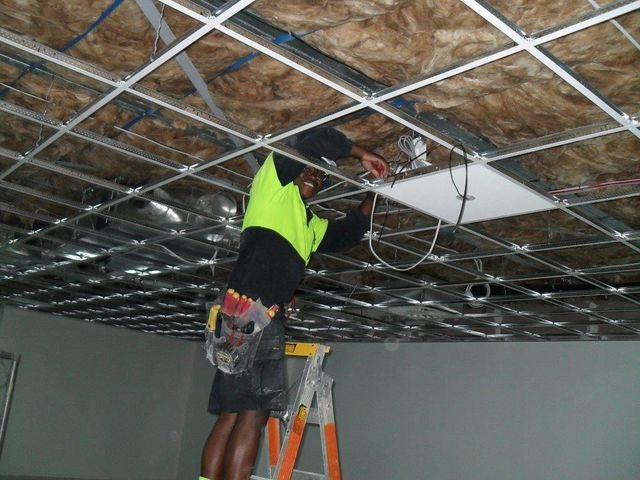 Electrician installing lighting in the office