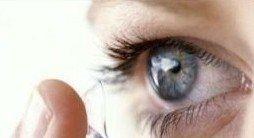 un occhio mentre si mette con l'indice una lente a contatto