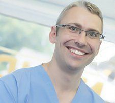 a male dentist smiling