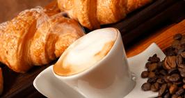 una tazza di cappuccino,chicchi di caffe' e brioches