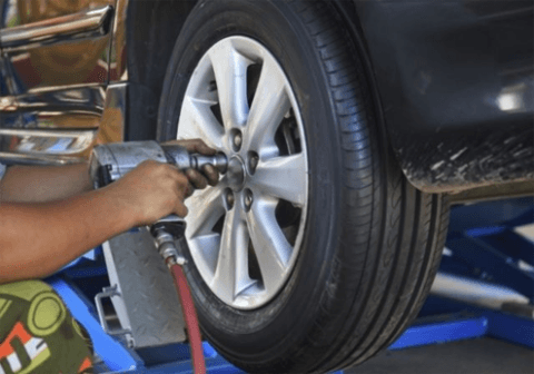 operaio cambia gomma in una macchina