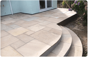 Curved patio with three steps leading down to the garden