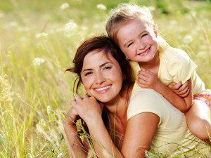 mother and daughter smiling in a field
