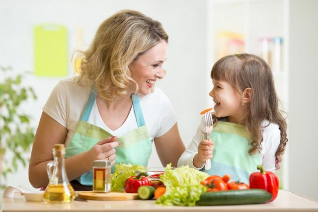 mother and daughter eating vegetables