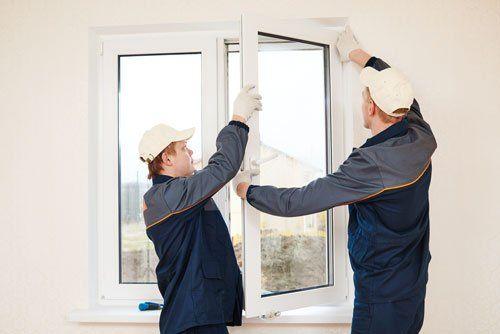 due uomini che stanno installando un'anta di una finestra