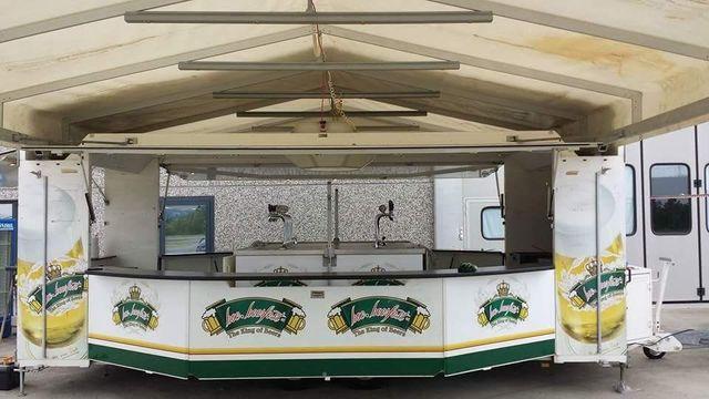 uno stand della birra con una tenda all'aperto