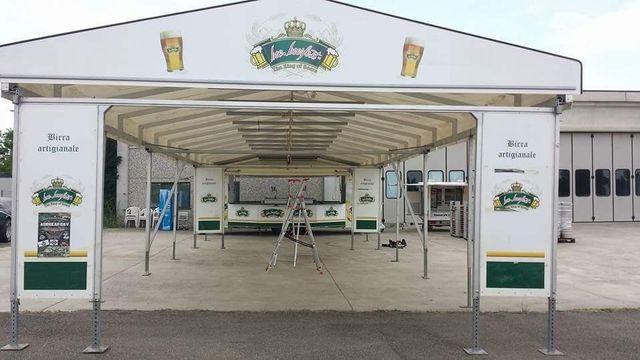 uno stand della birra artigianale con una tenda