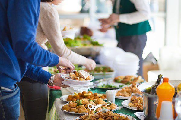 delle persone che si servono a un buffet con delle crocchette