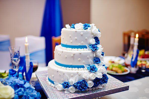 una torta a tre piani con una glassa bianca e delle rose