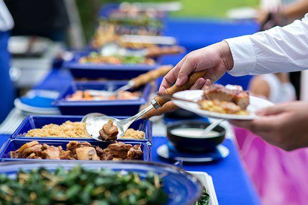 una mano che con un cucchiaio sui serve a un buffet