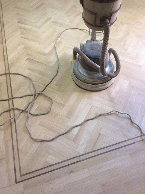 una smerigliatrice appoggiata su un pavimento in parquet