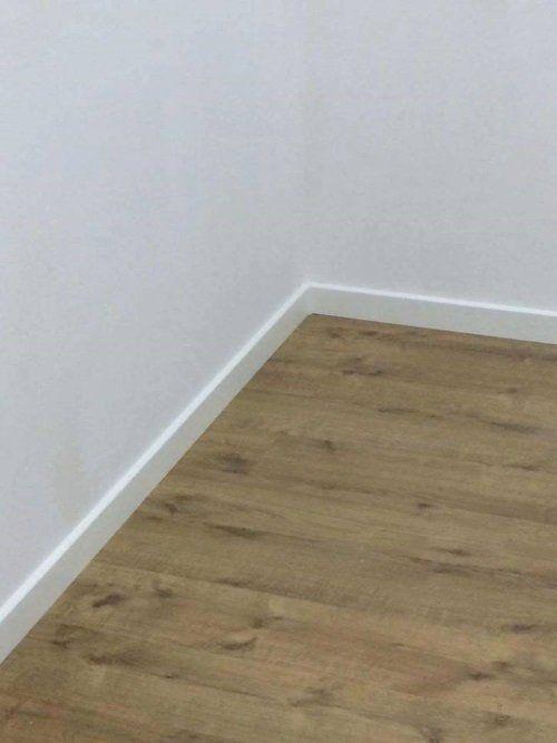 un angolo di una stanza con pavimento in parquet