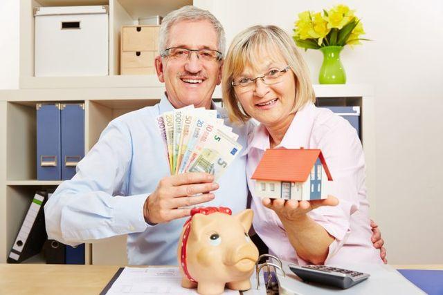 Coppia maggiore, un salvadanaio, una calcolatrice, una casa e denaro in mano