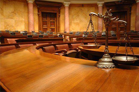 una bilancia a due piatti in un'aula di tribunale