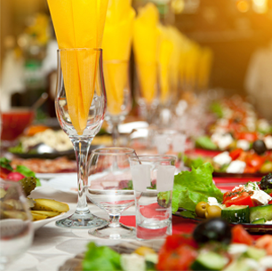 A table set with tapas, and yellow napkins in glasses
