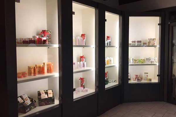 Serie di vetrine di cui una angolare con prodotti di bellezza e luci accese a Suzzara, MN