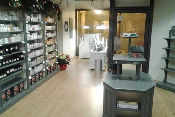 Interno del negozio L'erbolario con pavimento in parquet, sulla sinistra una vetrina con dei prodotti e al centro un mobile grigio con delle brochure a Suzzara, MN