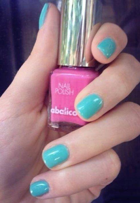 mano con dita smaltate di azzurro tiene in mano uno smalto rosa