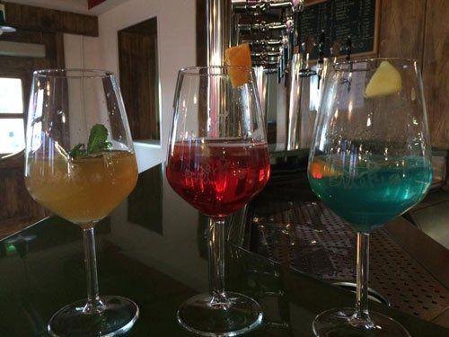 tre bicchieri con dei cocktail color arancione,rosso e azzurro