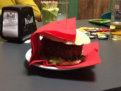 un piatto con un panino avvolto da un tovagliolo rosso