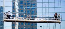 Operai puliscono i vetri di un alto palazzo dall'esterno su una piattaforma aerea