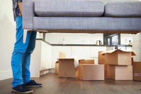Operai con il sofà in alto , si vedono molte casse, alcune aperte