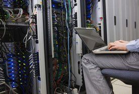 A man sitting in a computer server room with a laptop computer on his knee