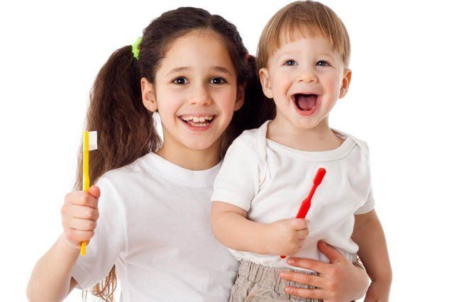 young boy and girl holding toothbrushes