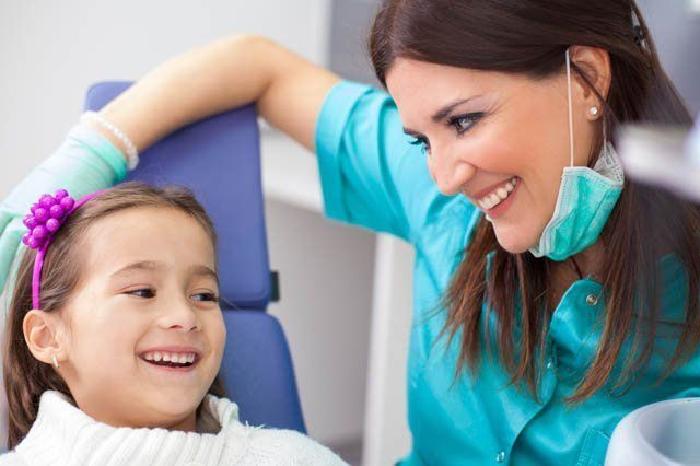 female dentist reassuring young girl