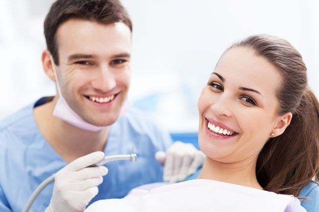 young male dentist with female patient