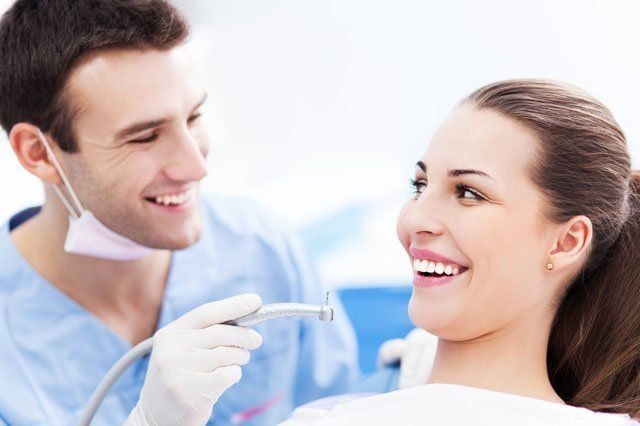 dentist smiling with patient in dental chair