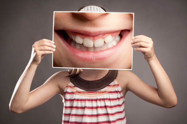 girl holding enlarged comic smile picture in front of face