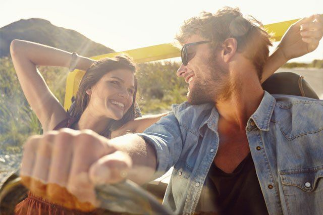 happy young couple in convertible car in sun