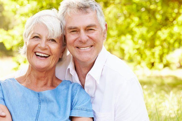 mature couple sitting in shade on grass