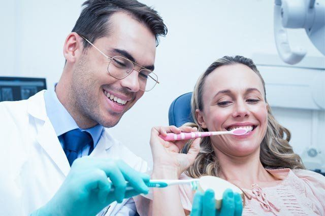 dentist showing woman how to correctly brush teeth